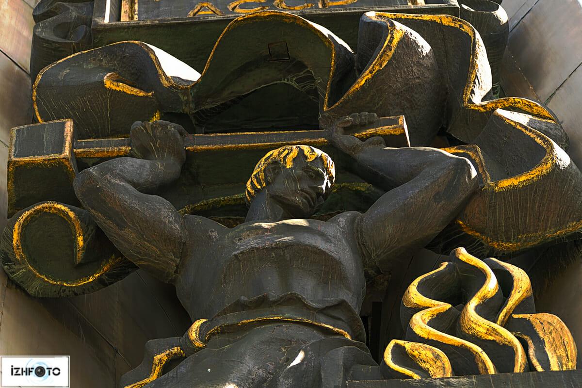 Между двумя пилонами, символизирующими Удмуртию и Россию, располагается множество позолоченных металлических рельефов, изображающих жизнь рабоче-крестьянского народа