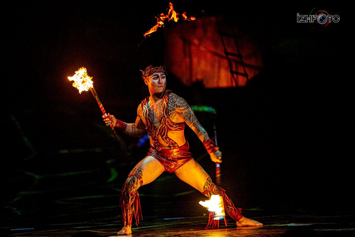 исполнитель вращает горящие ножи вокруг всего своего тела от ног до головы