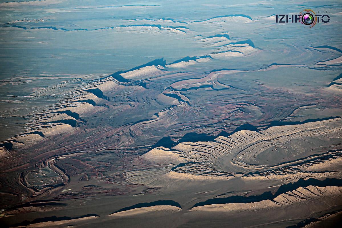 Виды из иллюминатора самолета в полете Фото